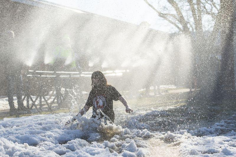 "Marist High School students run through a specially-designed ""polar cannon"" as a coronavirus-safe Polar Plunge alternative on Tuesday. Around 100 students participated."