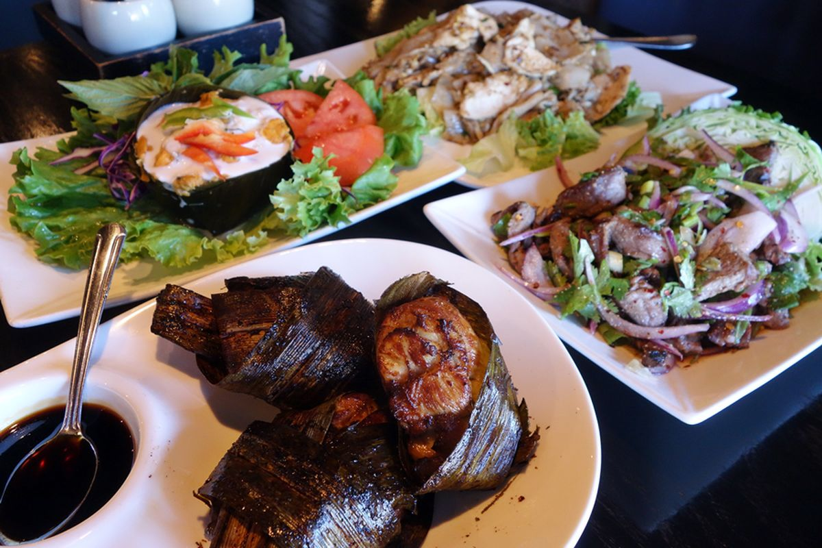 A view of a table with a variety of Thai meat and vegetable dishes from Bai Tong Thai Street Cafe.