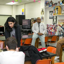 """High School Teachers, Ronell Whitaker, middle, and Eric Kallenborn, right, discuss potential comics to use in the classroom, while Kallenborn's chess club members, left, pour over a game at Alan B. Shepard High School in Palos Heights, Illinois, on Tuesday, April 4, 2017. Whitaker and Kallenborn founded Comic Education Outreach, a program partnered with Denver-based Pop Culture Classroom, which aims to """"help educators successfully incorporate comics and graphic novels into their classrooms,"""" according to their mission statement"""