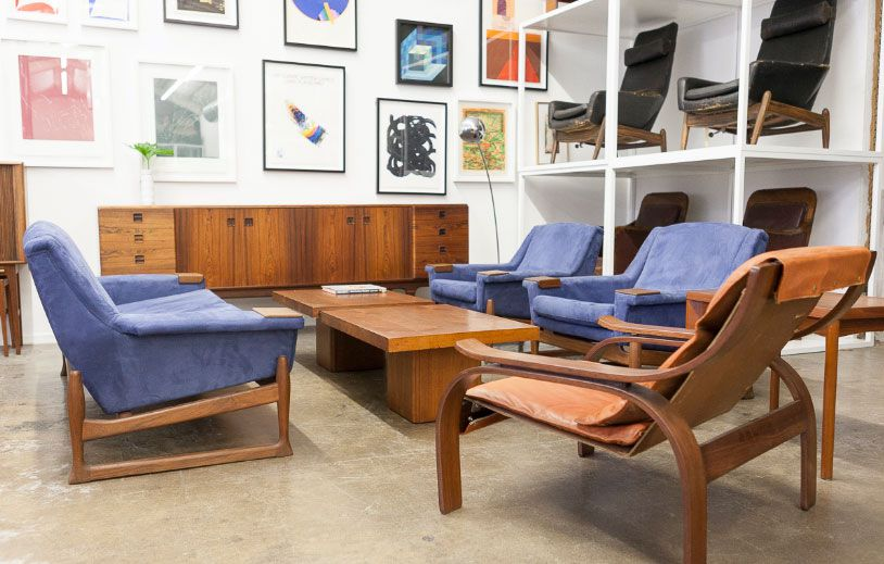 In a furniture store there are various assorted arm chairs, a desk, and shelves with other chairs on display. There are various works of art hanging on the wall.
