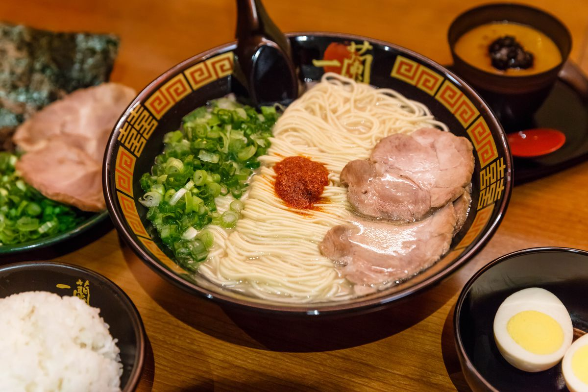 A bowl of ramen topped with scallions and chashu pork