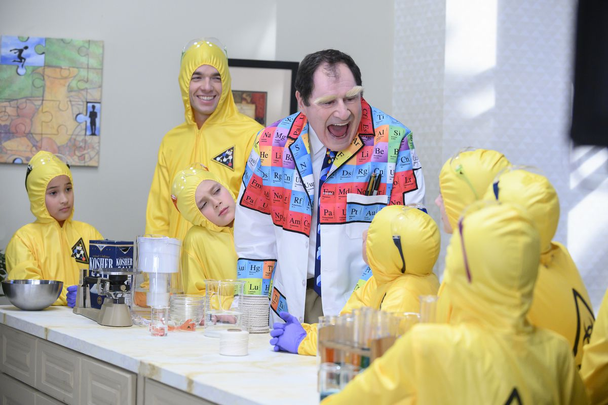 Richard Kind in a periodic table jacket laughs while Mulaney and kids dressed in yellow hazmat suits
