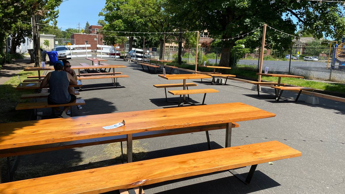 Picnic tables sit outside on the street of St Johns' Stormbreaker in Portland, Oregon