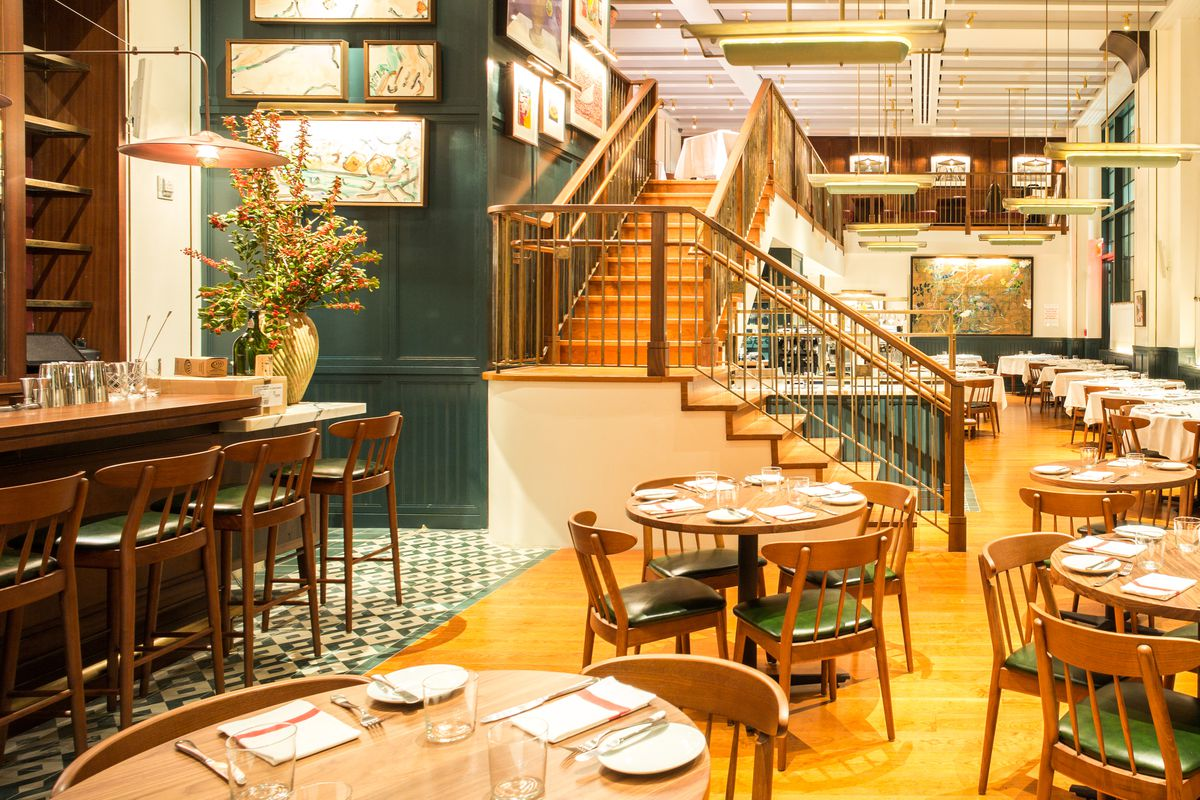 Round tables and chairs inside an empty restaurant dining room with stairs leading up to a second floor with more seating. A bar with chairs is on the left.