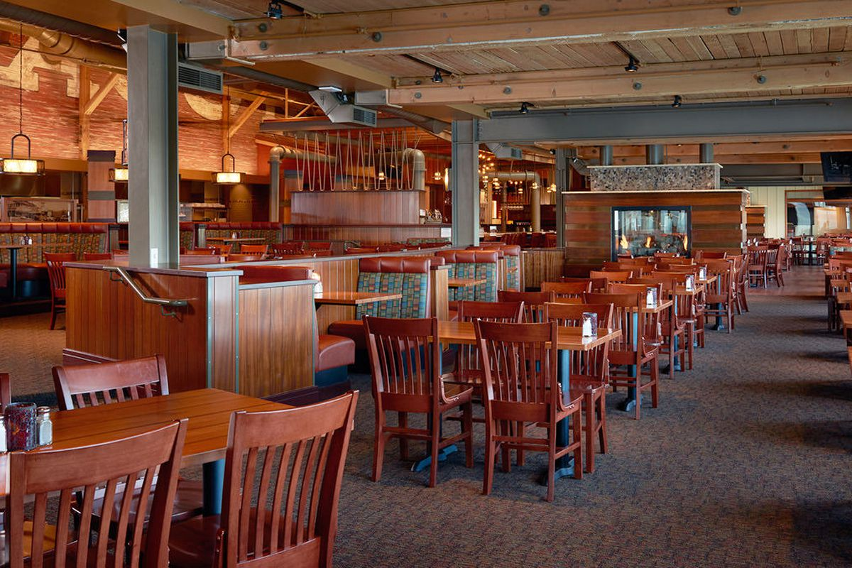 Tables and chairs in the empty, wood-accented dining room at Ivar's Acres of Clams, with a fireplace in the back