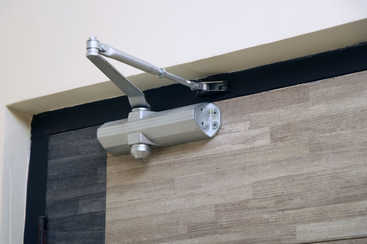 An automatic door closer attached to a multi toned wood door.