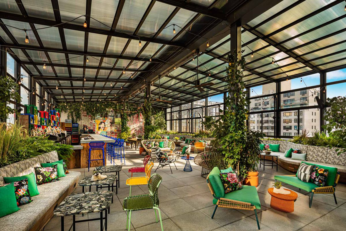 A rooftop lounge is outfitted with colorful couches, chairs, communal tables, and in the background, a view of New York City skyscrapers