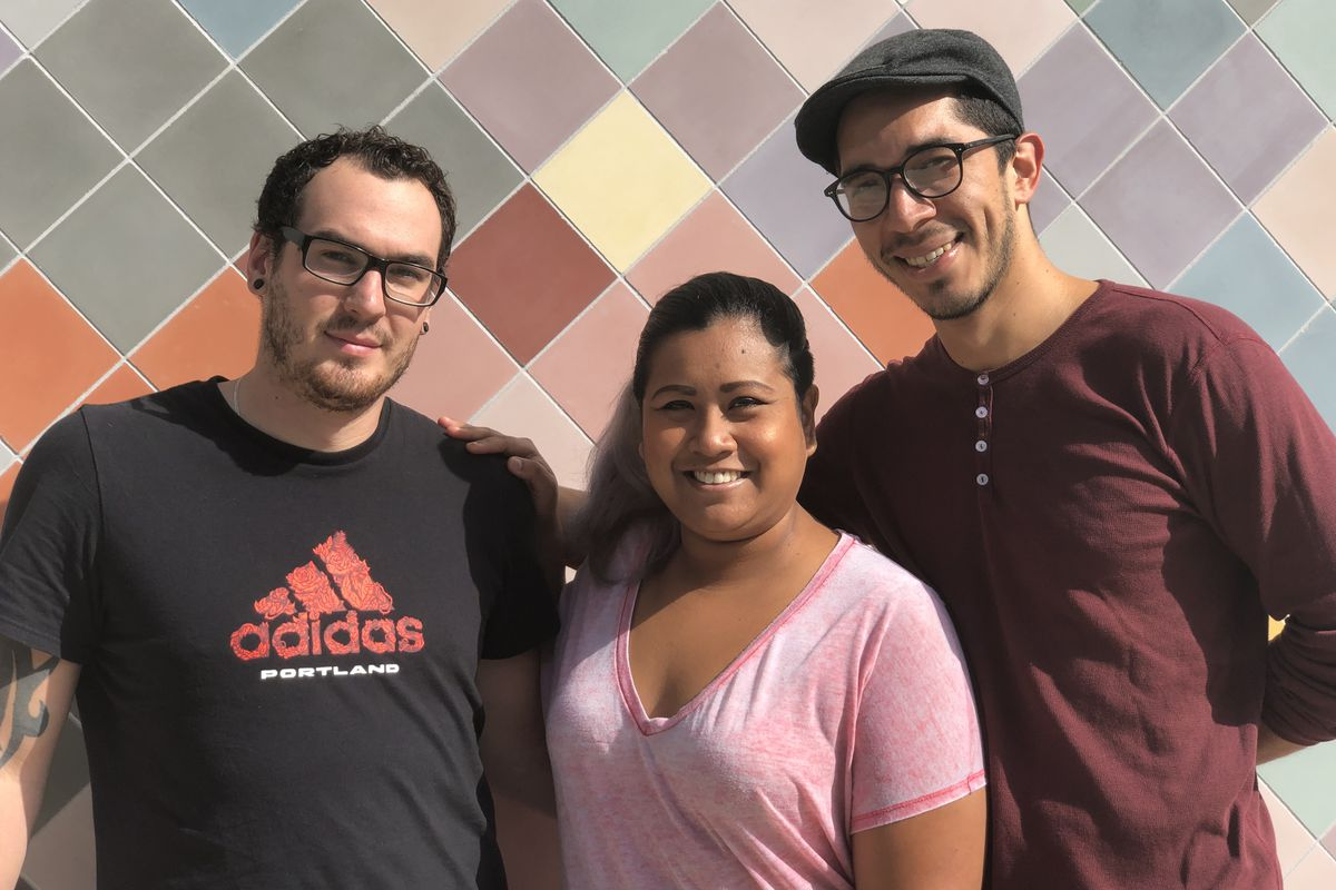 A picture of three people standing in front of a colorful wall at Mestizo