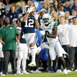 Brigham Young Cougars wide receiver Puka Nacua (12) hauls in a long pass ahead of South Florida Bulls defensive back Daquan Evans (0) as BYU and USF play a college football game at LaVell Edwards Stadium in Provo on Saturday, Sept. 25, 2021.