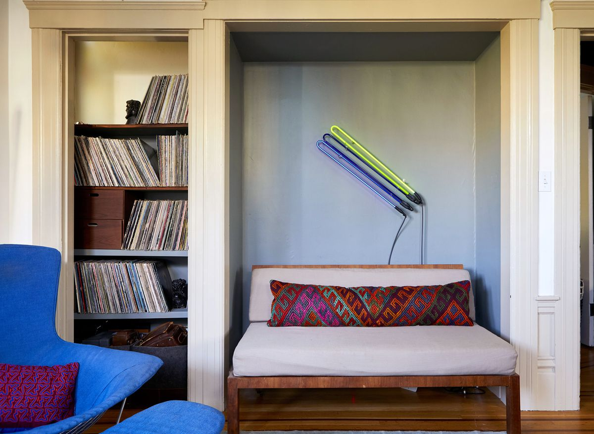 A living area. There is a grey couch with a long patterned pillow. There are shelves full of records. There is a bright blue arm chair with a purple pillow.