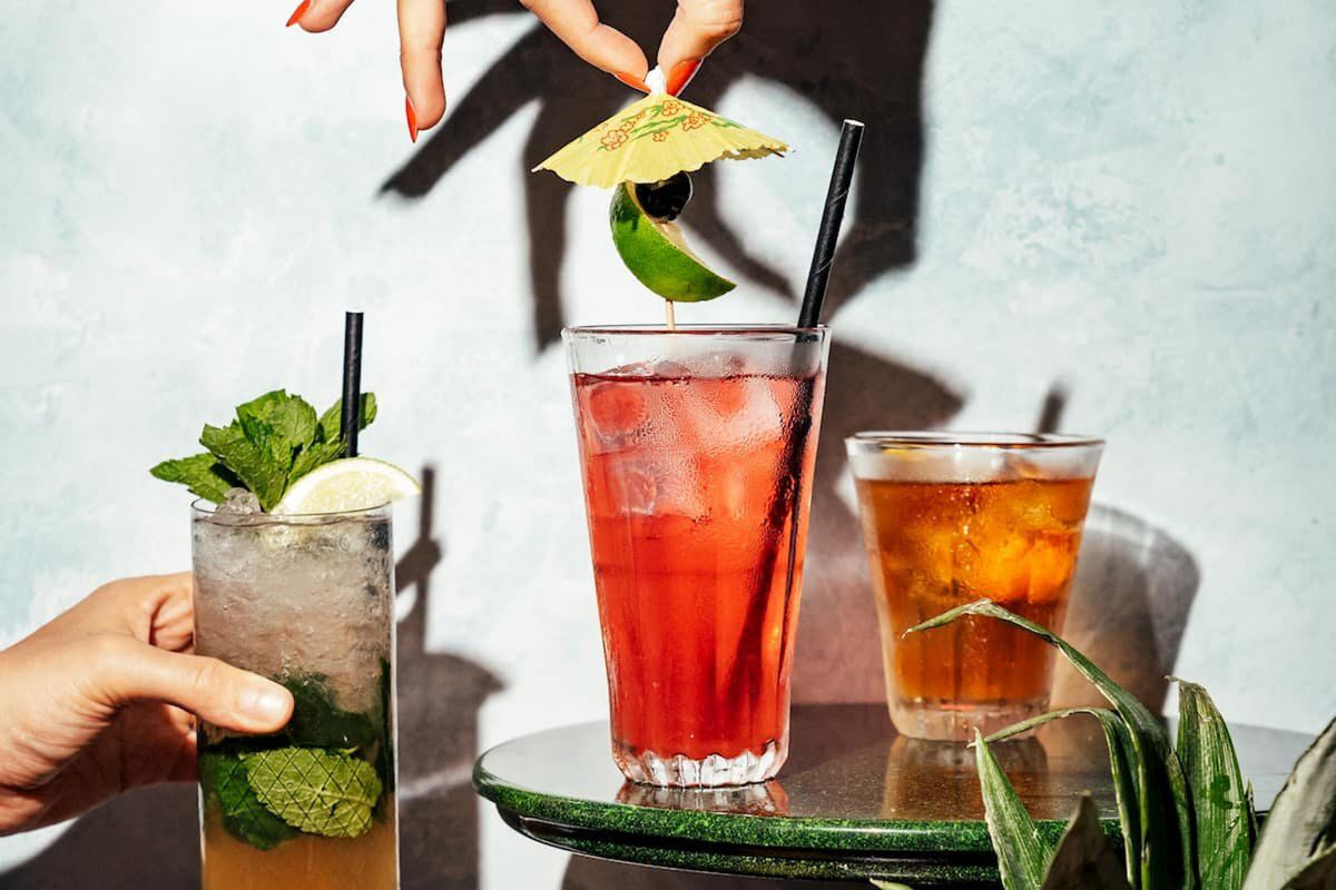 Three cocktails, from left-to-right, the left mojito held up by a hand, the centre having a cocktail umbrella dropped in, and the right-hand perched on a stool