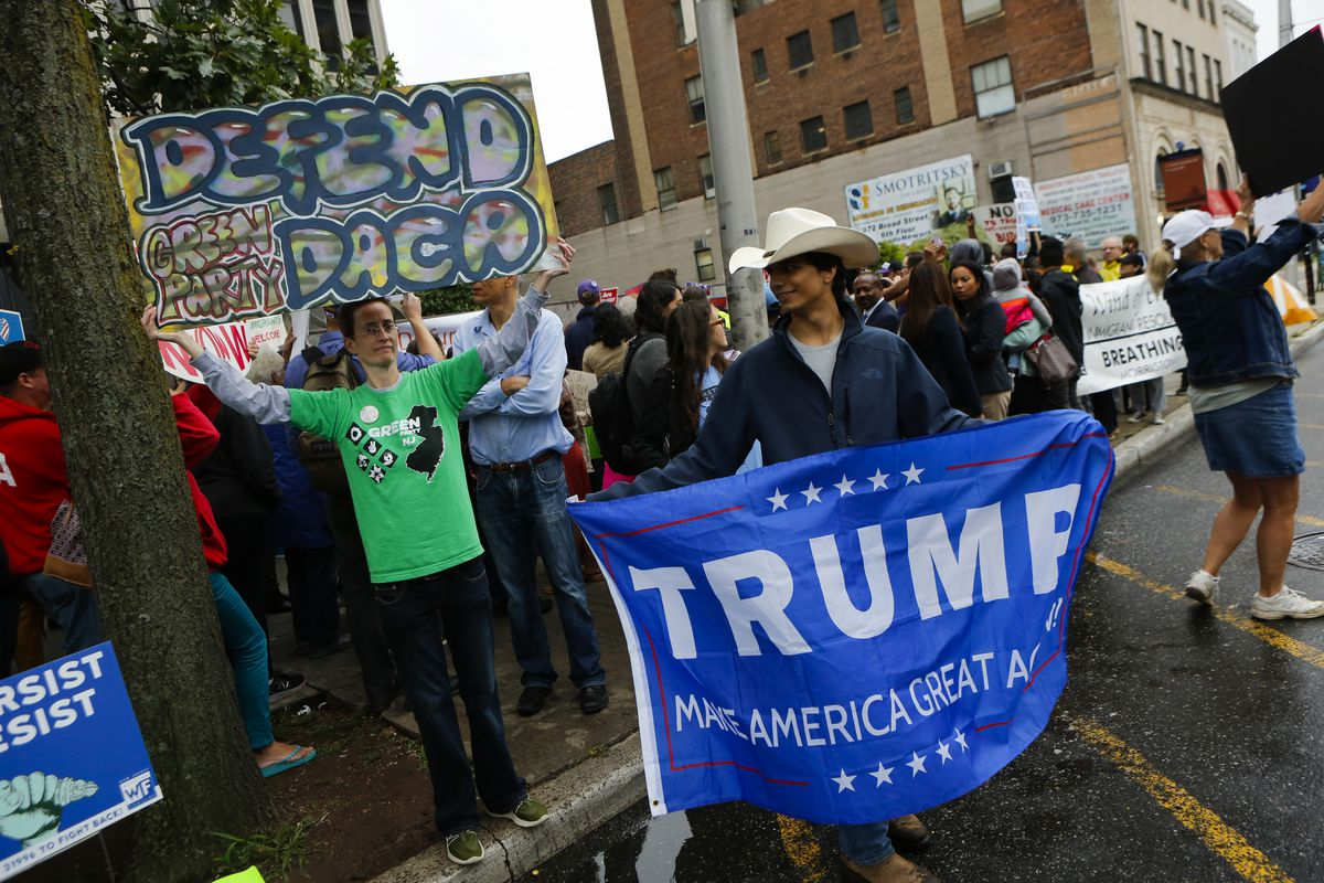 """Acitvists hold """"Defend DACA"""" signs at a rally against President Trump's decision to deport Dreamers."""