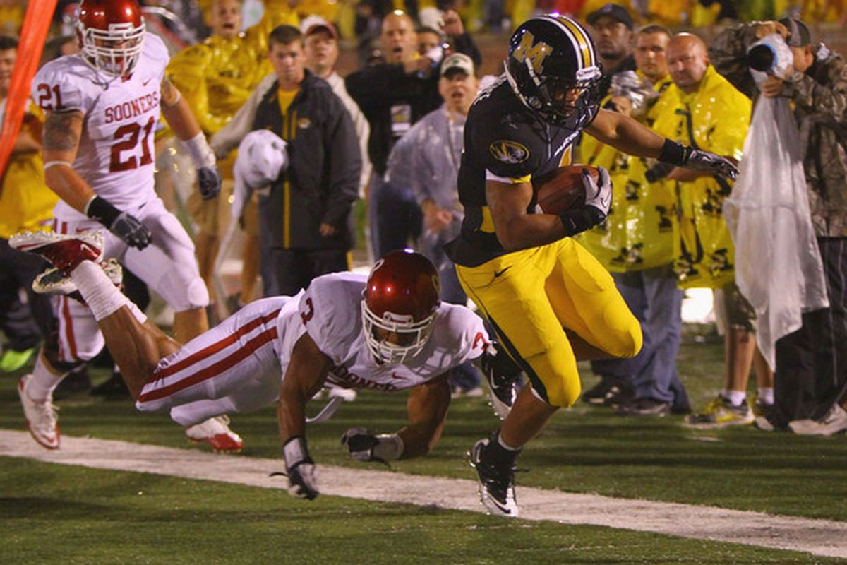 COLUMBIA MISSOURI - OCTOBER 23: Kendial Lawrence #4 of the Missouri Tigers gets past Jonathan Nelson #3 of the Oklahoma Sooners at Faurot Field.  (Photo by Dilip Vishwanat/Getty Images)