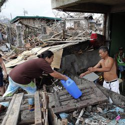 Thelma Caones reaches water to her husband Romeo as they make their way through the rubble to their home in Tacloban, Friday, Nov. 22, 2013. At left is their daughter Rachel.