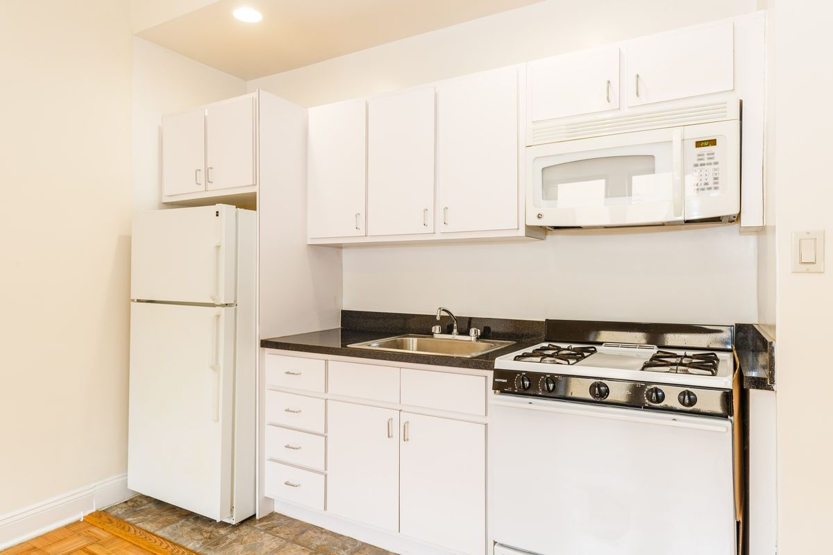 A kitchen with white cabinetry, hardwood floors, and base moldings.