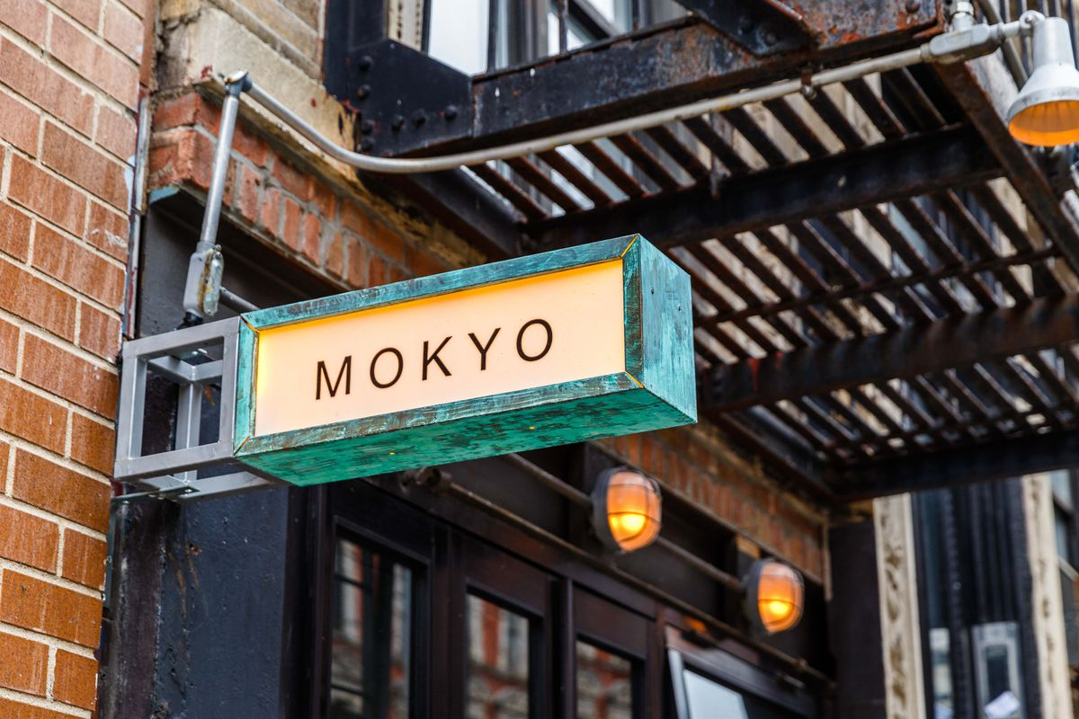"""A yellow sign out front of the restaurant is bordered in green with the word """"MOKYO"""" in capital letters"""