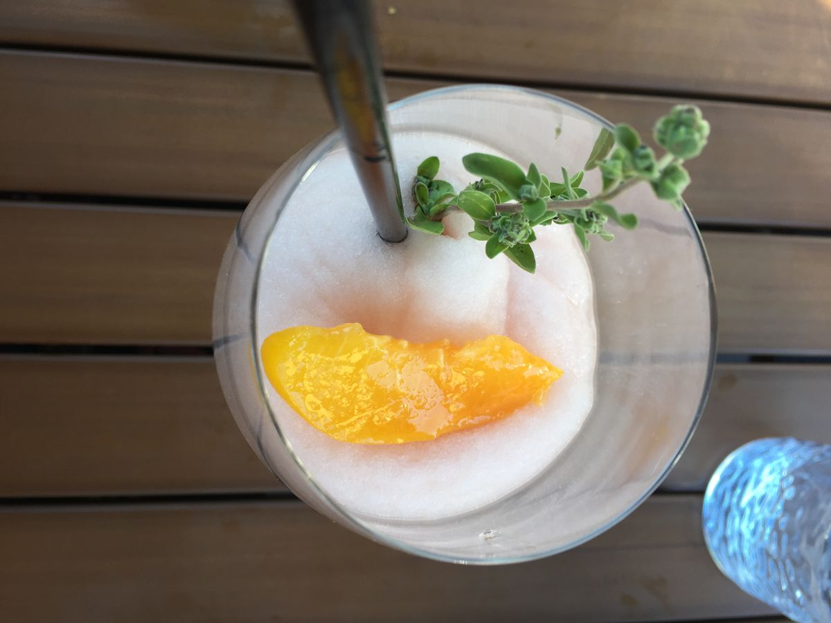 Close up of a glass filled with pink slush, a peach slice and a sprig of thyme
