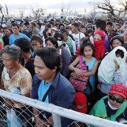 People wait in line at the airport, seeking passage on military transport planes to leave Tacloban, Tuesday, Nov. 19, 2013, following a typhoon in the Philippines.
