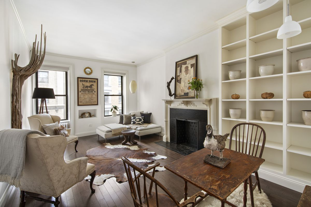 A living room with hardwood floors, a small dining table with two chairs, built-in bookshelves, two windows, and a decorative fireplace.