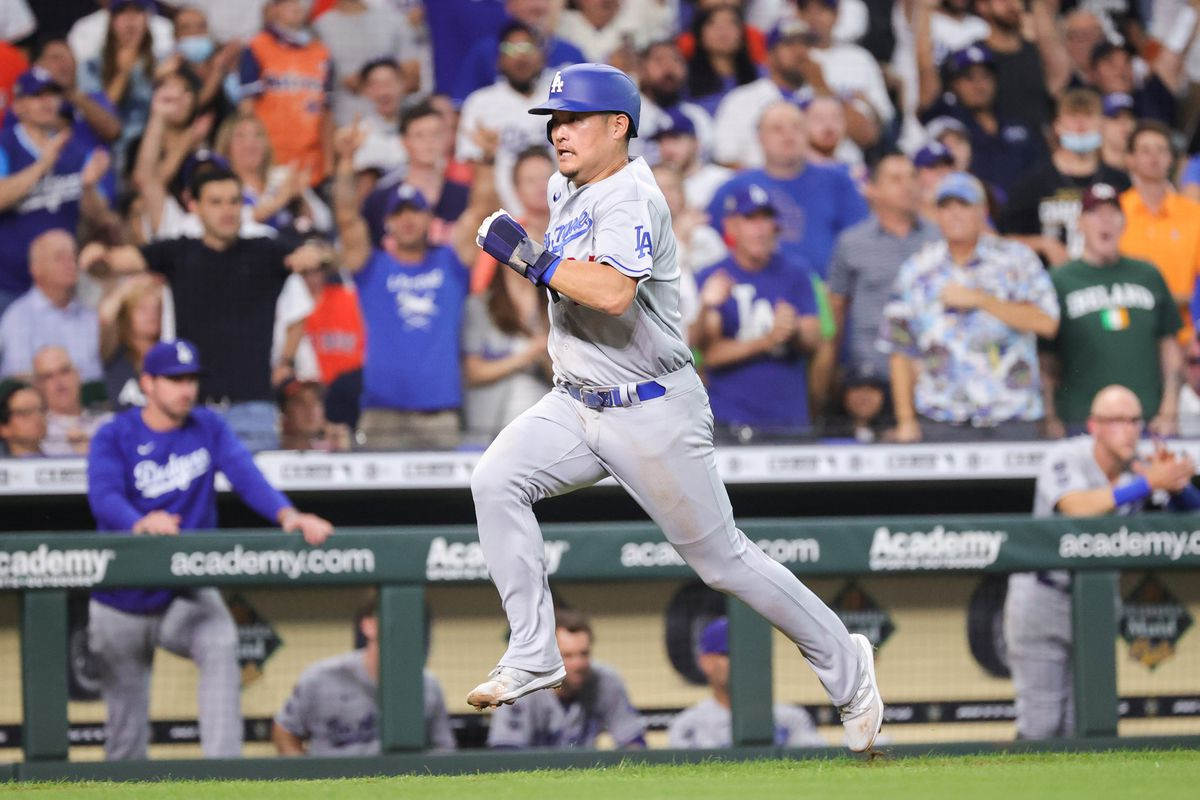 Yoshi Tsutsugo #28 of the Los Angeles Dodgers runs towards home plate during the third inning on a single hit by Max Muncy #13 against the Houston Astros at Minute Maid Park on May 26, 2021 in Houston, Texas.