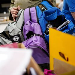 Air Force Tech. Sgt. Jeremy McNeel, of the U.S. Air Force 729th Air Control Squadron, loads up backpacks with free school supplies during Operation Homefront's annual Back-to-School Brigade event at Hill Field Elementary in Clearfield on Tuesday, Aug. 13, 2019.