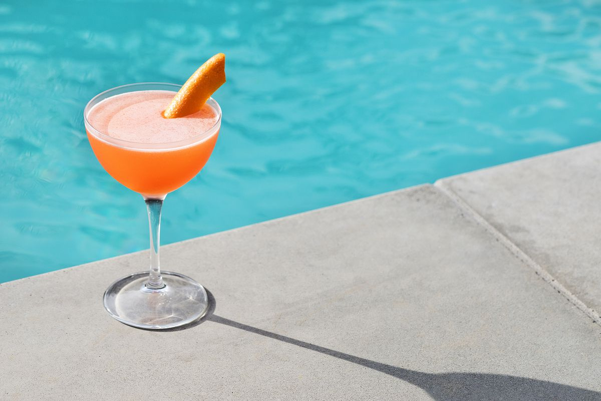 An orange cocktail in a tall glass sits next to a shimmering pool.