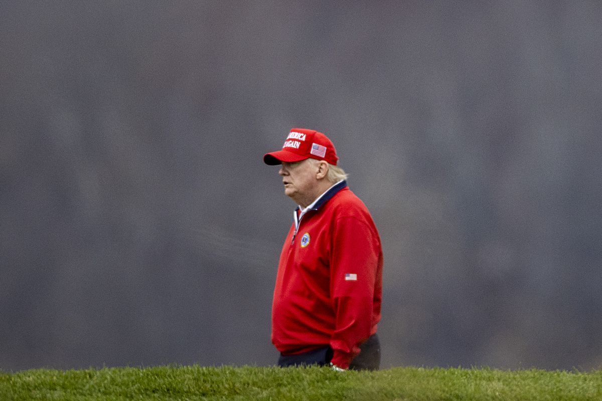Trump in a red Make America Great Again baseball cap and a matching red jacket bearing the seal of the president of the United States, walks across a green on a cloudy day.