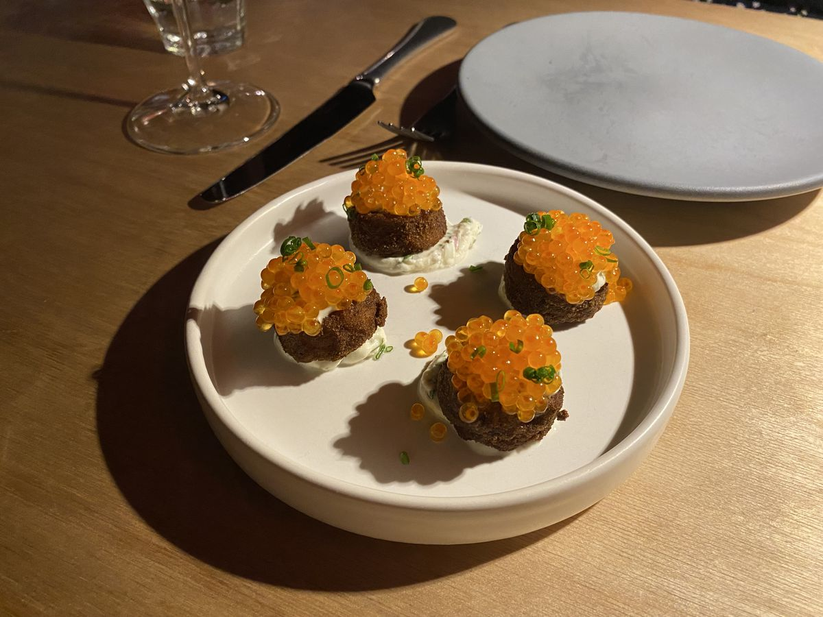 Four dark brown croquettes perched on mounds of creme fraîche are topped in orange trout roe.