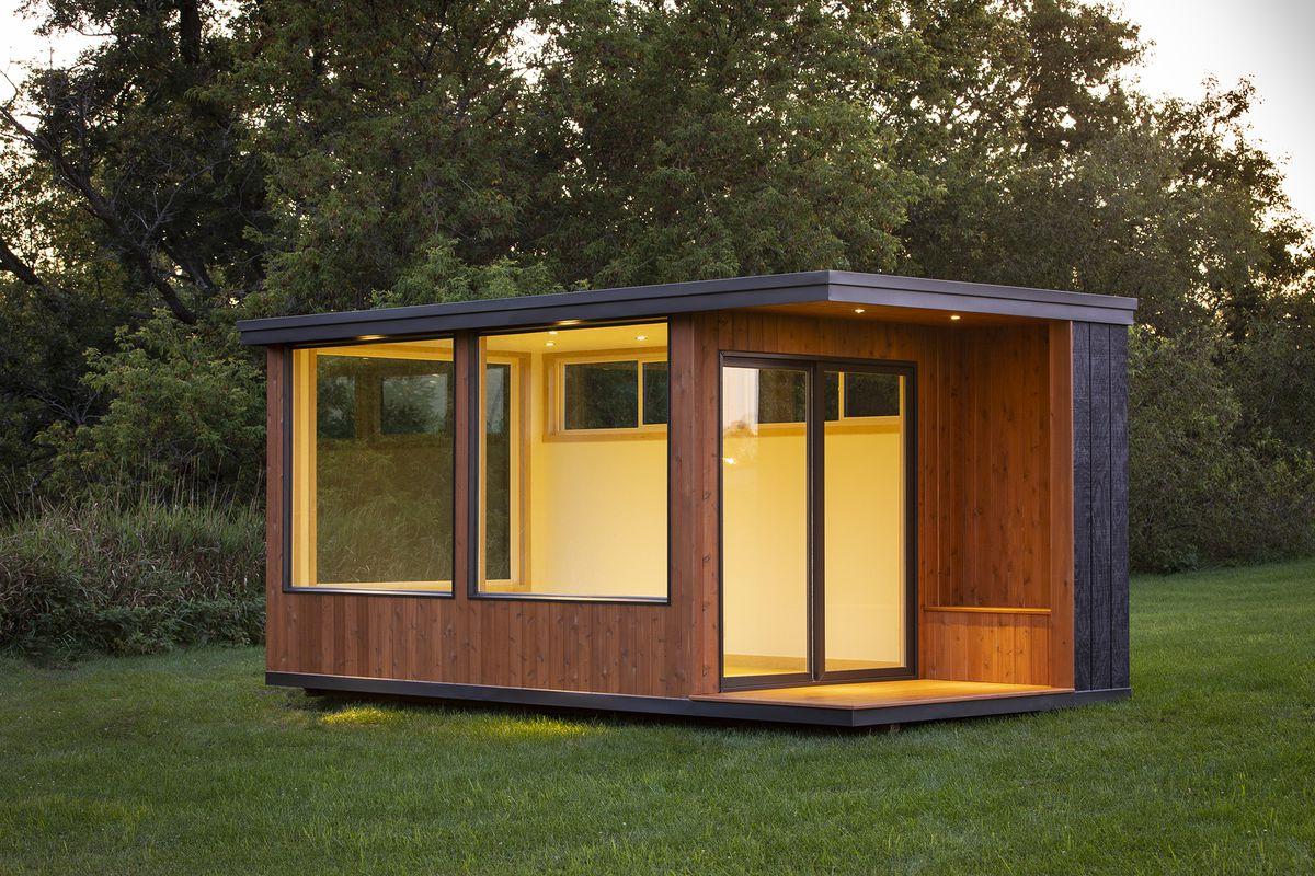 A boxy small dwelling with large glass windows.