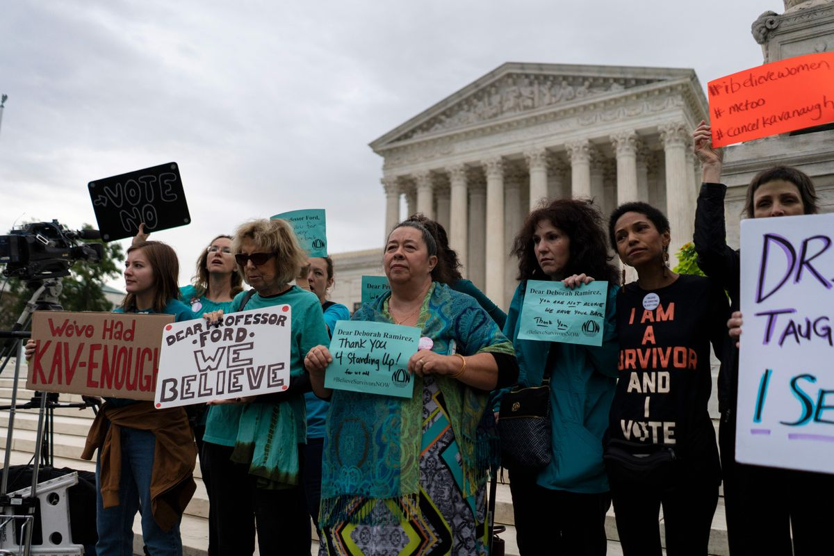 Women stand in front of the Supreme Court building holding signs.