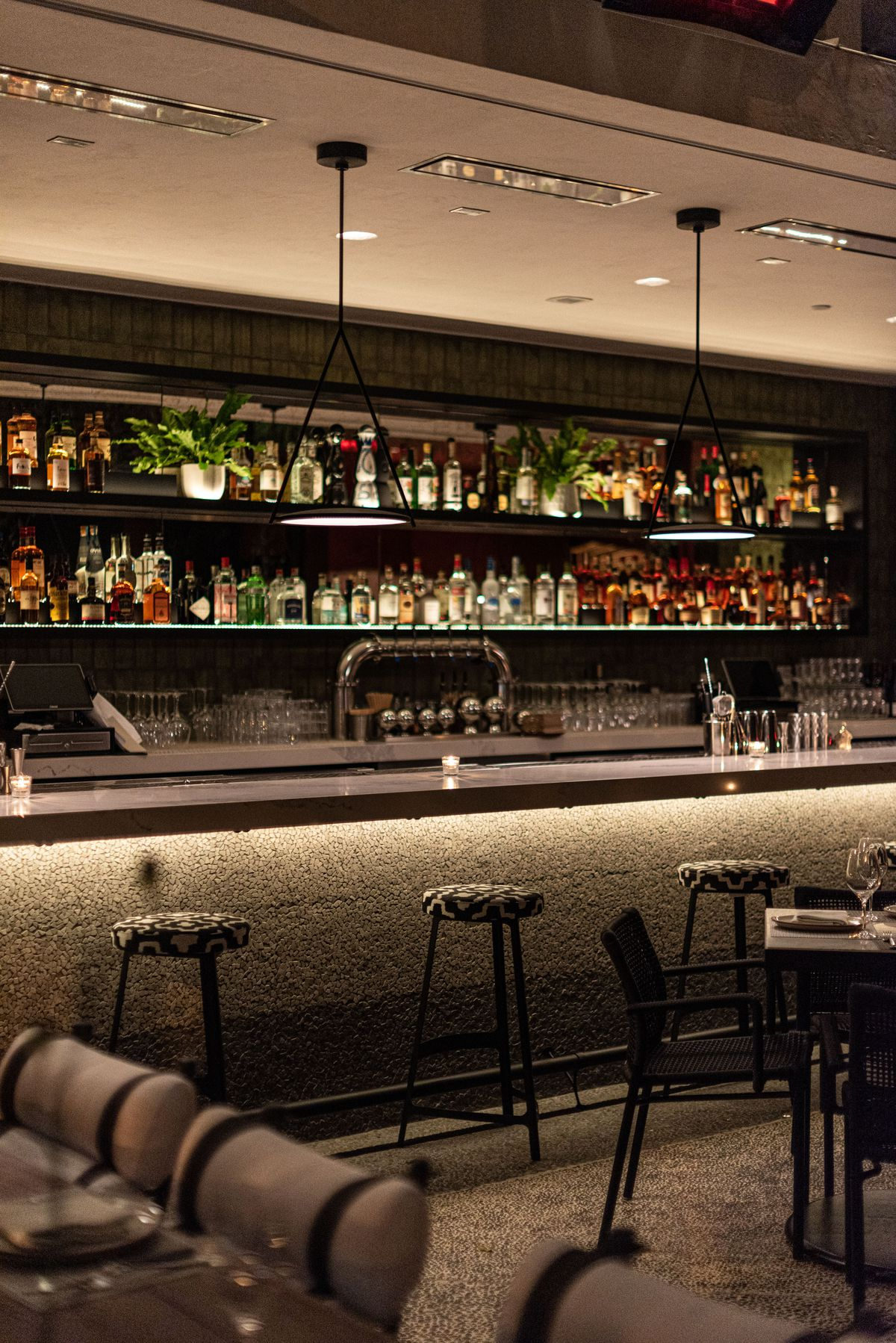 A dark bar with lots of bottles behind a backlit bartop, with stone underfoot.