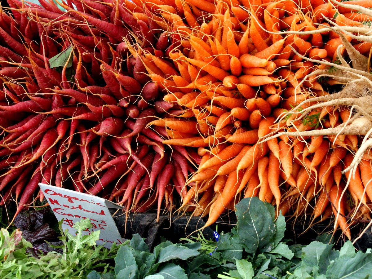 A Los Angeles farmers market stand with stacks of purple and orange carrots for sale.