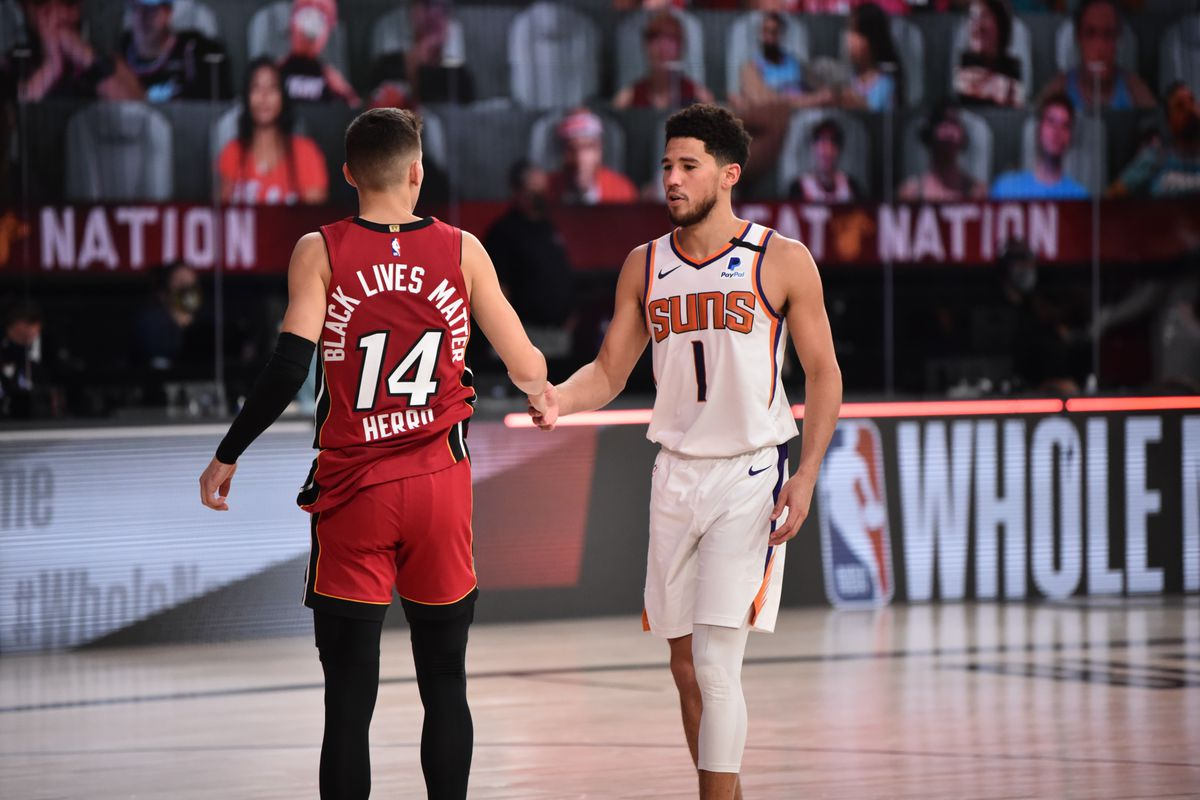 Tyler Herro of the Miami Heat and Devin Booker of the Phoenix Suns hi-five after the game on August 8, 2020 at Visa Athletic Center at ESPN Wide World of Sports in Orlando, Florida.