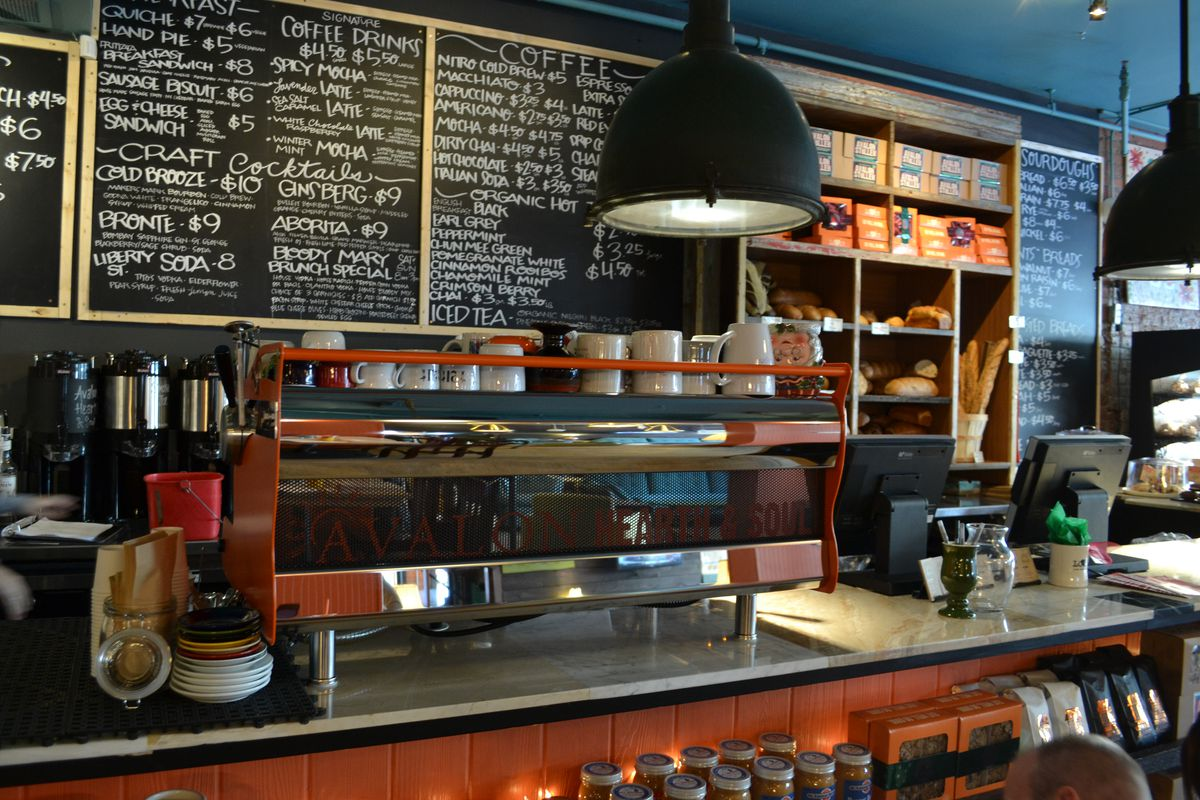 The bar at Avalon features an orange espresso machine and chalk menu boards.