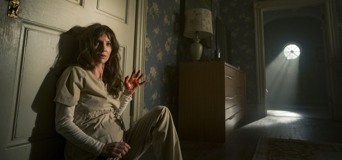 Annabelle Wallis sits on the floor of a bedroom looking terrified in Malignant