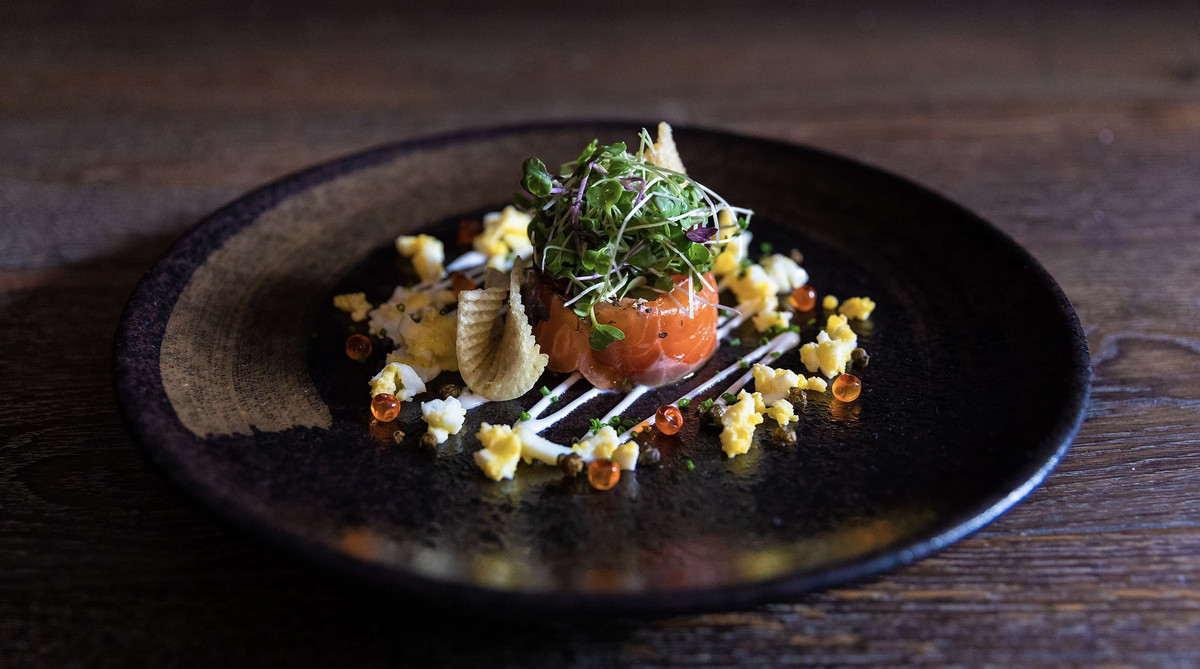 Salmon tartare at Chapeau. A small piece of salmon with sprouts on top and colorful adornments on the plate, including roe.
