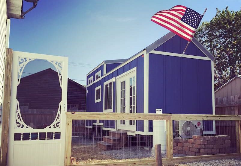 The exterior of a tiny house in Virginia. The facade is blue with white decorative details. There is a United States flag attached to the house.
