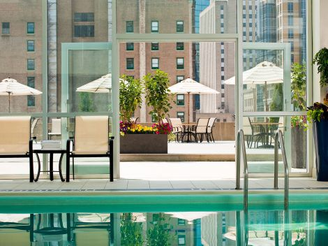An indoor pool with floor to ceiling windows. The windows overlook a lounge area.