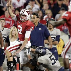 Wisconsin quarterback Joel Stave (2) throws as he is hit by Utah State's Zach Vigil (53) during the second half of an NCAA college football game Saturday, Sept. 15, 2012, in Madison, Wis. Wisconsin won 16-14.