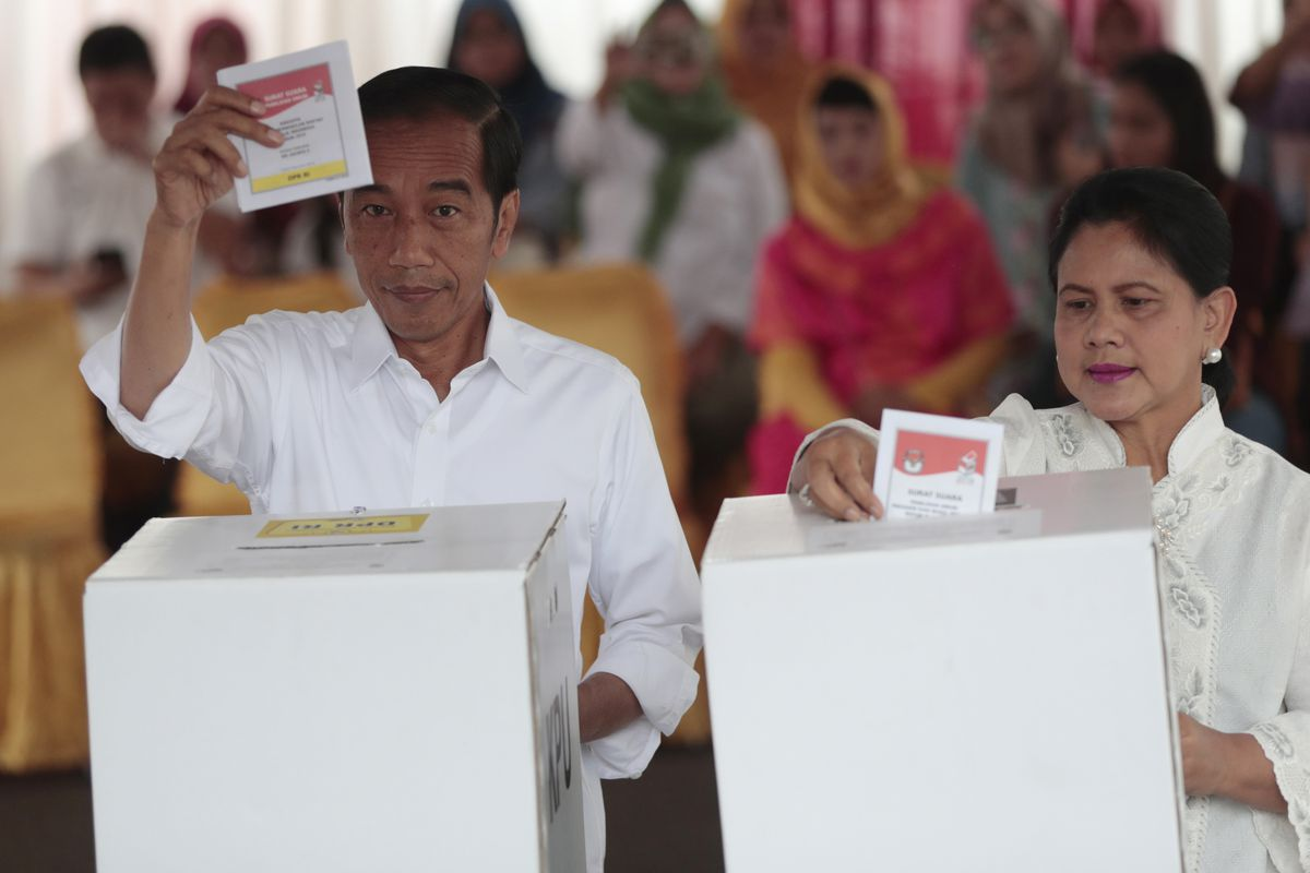 """Indonesian President Joko """"Jokowi"""" Widodo and his wife Iriana cast their ballots during the election at a polling station in Jakarta, Indonesia, Wednesday, April 17, 2019. Tens of millions of Indonesians were voting in presidential and legislative electio"""