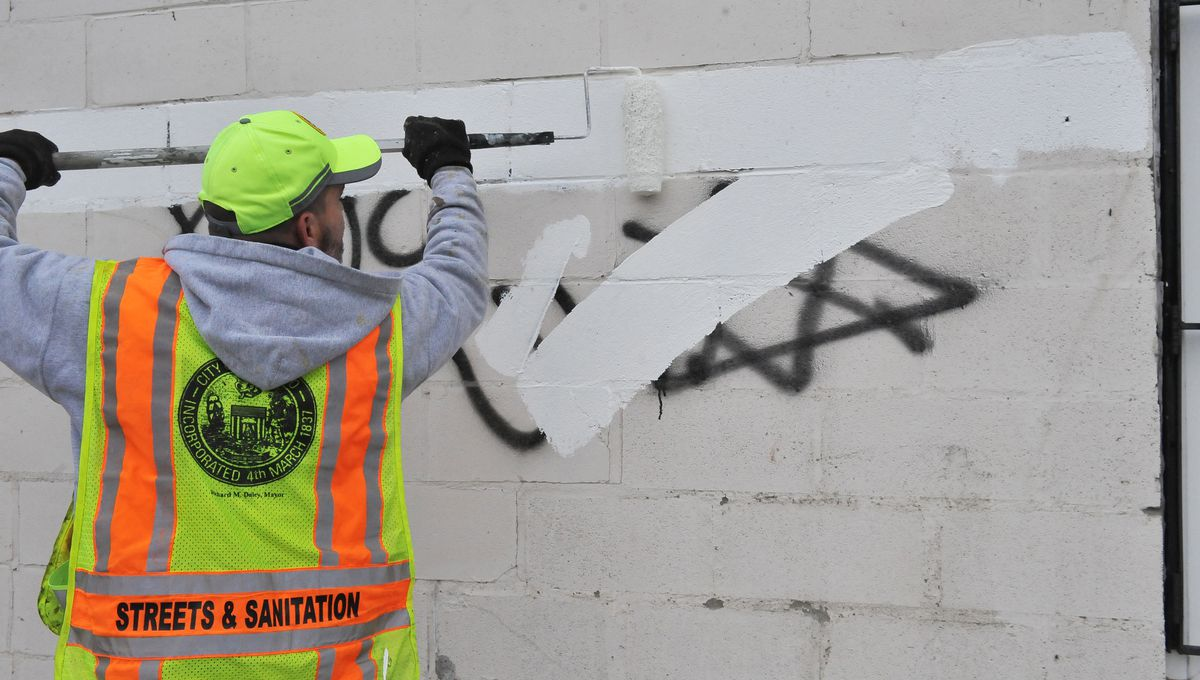 Workers from  Chicago Steets and Sanitation remove anti-Semitic graffiti in 2014.  |Sun-Times file photo
