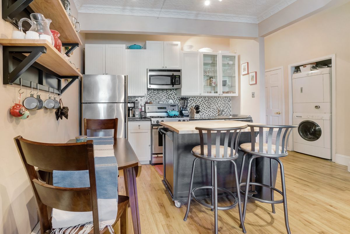 A kitchen with hardwood floors, beige walls, a table and a small kitchen island.