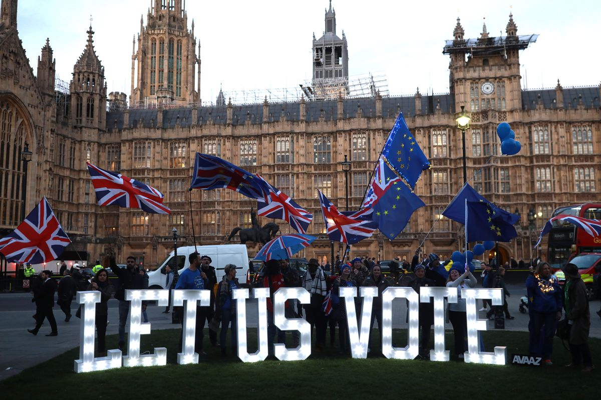 Brexit protesters stand by light up letters that read 'Let us vote', outside the Houses of Parliament on March 27, 2019 in London, England.