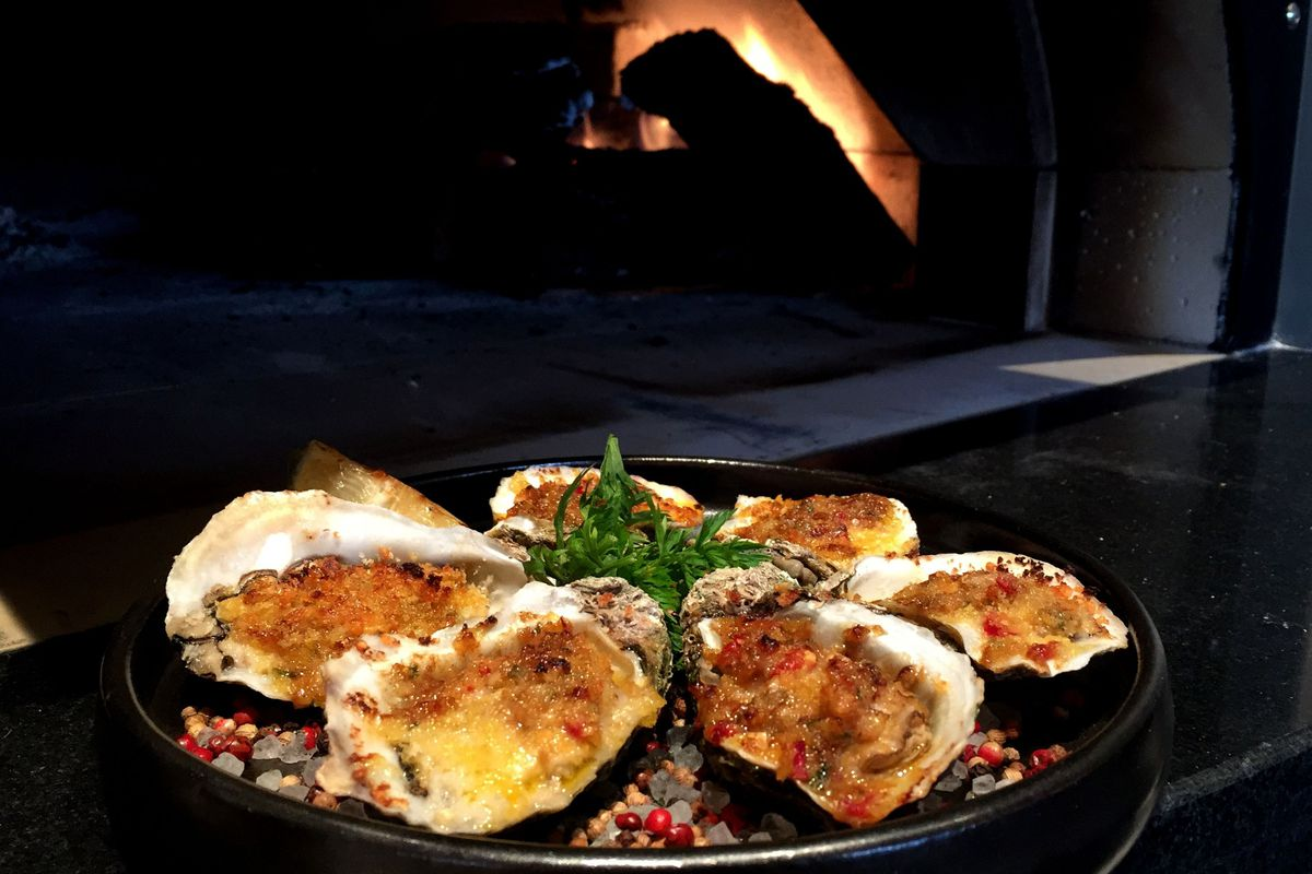 six chargrilled oysters on a plate with a large fireplace in the background