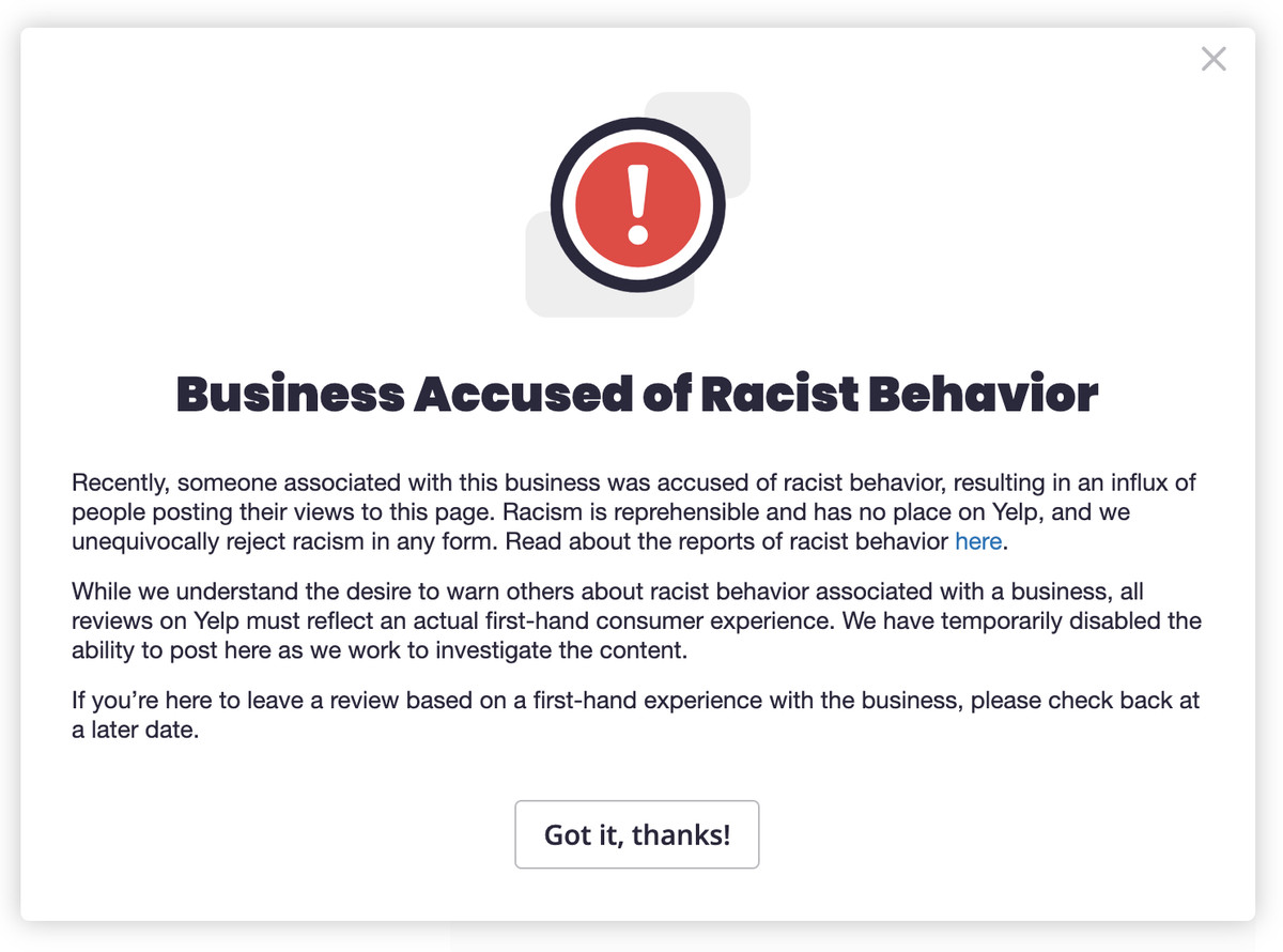 "Yelp alert with a red exclamation point and the name ""Business Accused of Racist Behavior."""