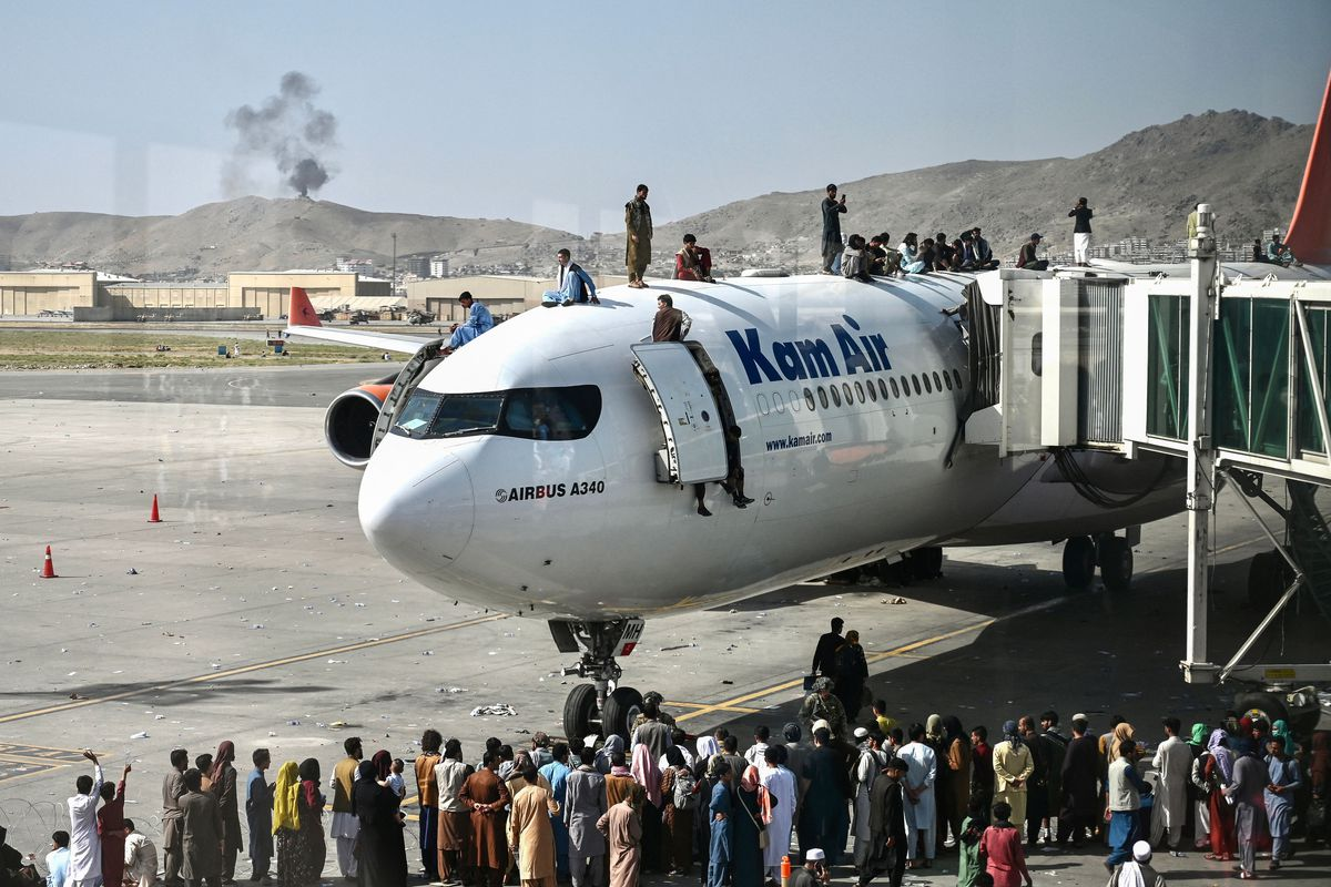 Afghan people climb atop a plane as they wait at the Kabul airport on Monday, after a stunningly swift end to Afghanistan's 20-year war, as thousands of people mobbed the city's airport trying to flee the group's feared hardline brand of Islamist rule.