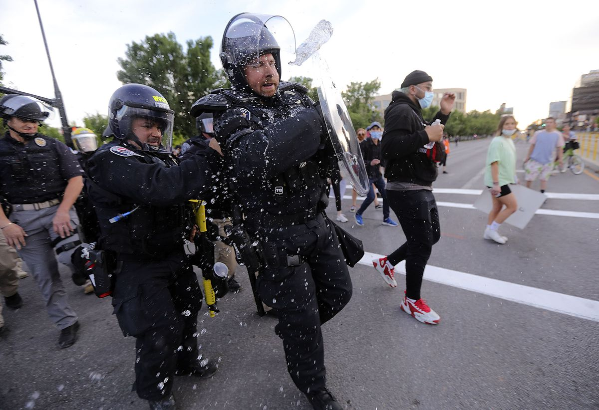 A police officer is hit with a bottle of water as police try to enforce a curfew and clear protesters out of downtown Salt Lake City on Monday, June 1, 2020. Recent protests against police brutality, racial discrimination and the killing of George Floyd turned violent in Salt Lake City and other cities across the nation, prompting Gov. Gary Herbert to call in the Utah National Guard.