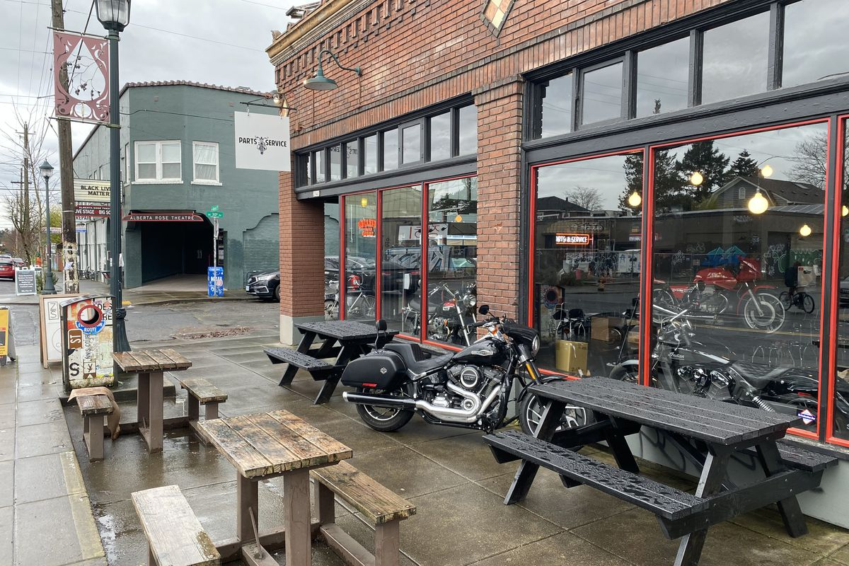 """A brick building on a rainy street corner with a sign reading """"Parts and Services"""" is filled with motorcycles. A motorcycle and some picnic tables are parked outside."""