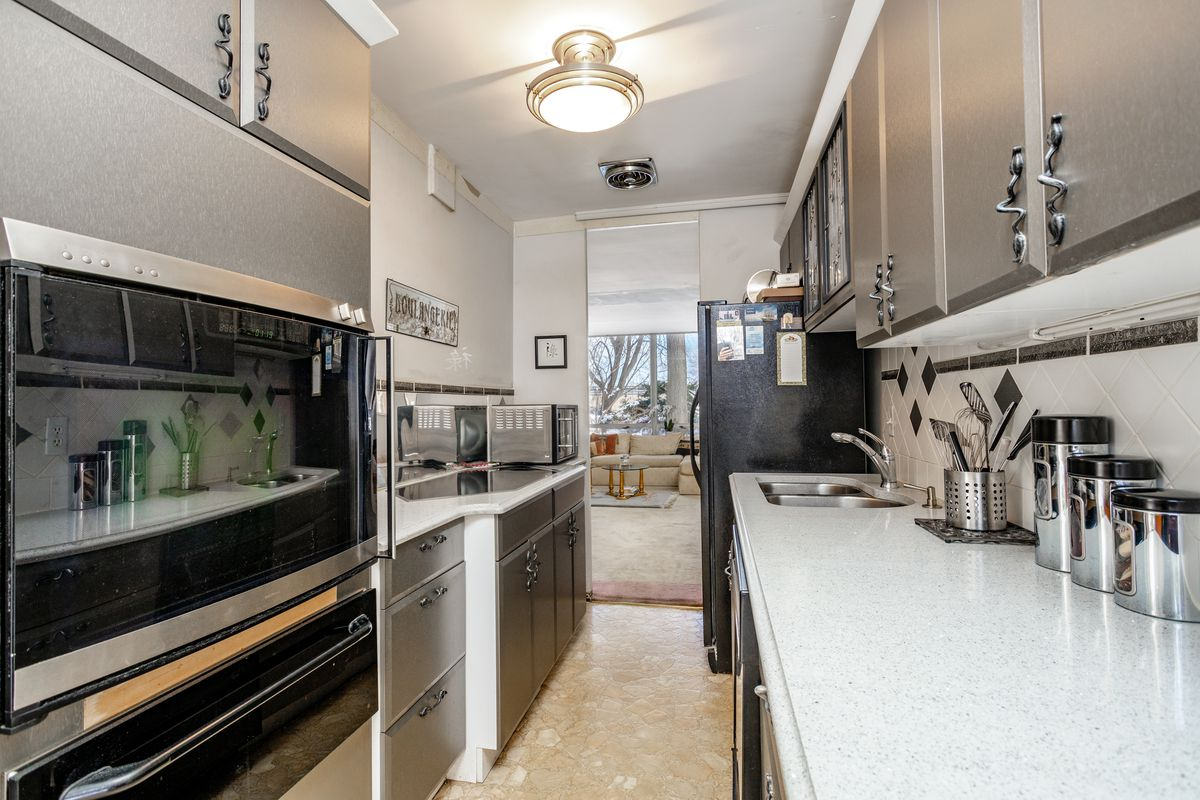 A galley kitchen with metal cabinets and white countertops.