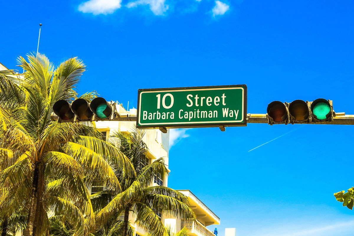 A traffic light in Miami Beach with palm trees in the background